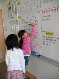 Kids are responssible for recording attendance in the teacher's office-here an older student watches a first grader